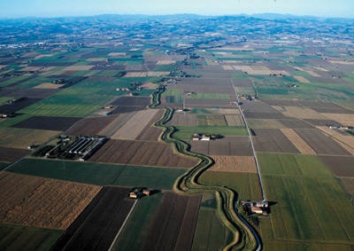 The small river Gaiana snakes through cultivated fields in the upper Po plain (Bologna province). The Appennines reliefs are visible in the background.